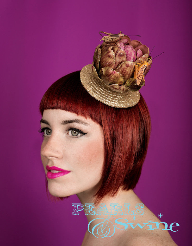 A quirky, cute artichoke set on a light-gold glitter fascinator base decorated with grasshoppers feasting on the artichoke. It is backed with leopard-print satin and attaches with a comb and adjustable hat elastic.  This limited edition whimsical hat is ideal for vegetarians and insect lovers.