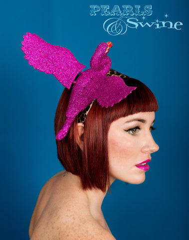Flamboyant fuchsia pink glittered flamingo set on a wide leopard print satin headband. The wings even move slightly when you walk!!  Perfect for Ascot Ladies Day, The Doncaster Races, York Races, Kentucky Derby or an Alice in Wonderland inspired costume.