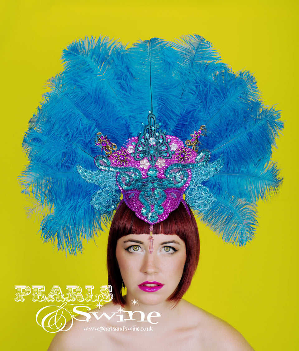OTT carnival style, burlesque showgirl turquoise blue ostrich feather headdress set on a hand blocked felt base covered in fuchsia pink glitter and decorated with lace, sequin, gems and jewels. This is set on a wide headband, should you require any extra securing bobby pins will be fine.