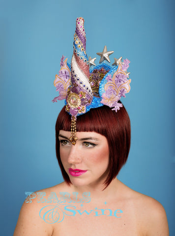 One of a kind detailed unicorn headdress, complete with a bejewelled unicorn horn, ears with lace detailing and silver stars. And a central jewel detail that drips from the front.  This unicorn headdress is hand blocked, backed with leopard print satin, and attaches with a comb and adjustable hat elastic.  Ideal surreal headpiece of wearable art for lovers of ponies and unicorns.  Disclaimer: No unicorns were harmed in the making of this piece!
