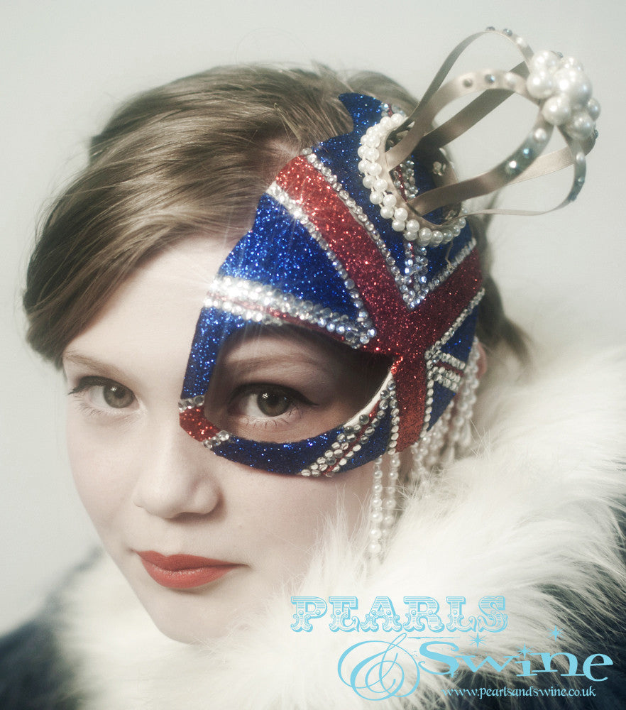"Union Jack Half Mask Fascinator ""Regency""  This half mask fascinator has a  glittered Union Jack with a gold crown decorated in pearls, crystals, and pearl beading. Attaches with a comb."