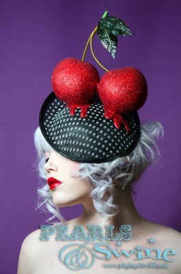Huge cherries covered and dripping beautiful red glitter on a vintage style polka dot sinamay hat. This hat is set on a hidden base which attaches easily with a comb and adjustable hat elastic. Perfect headpiece for the races or a wedding.