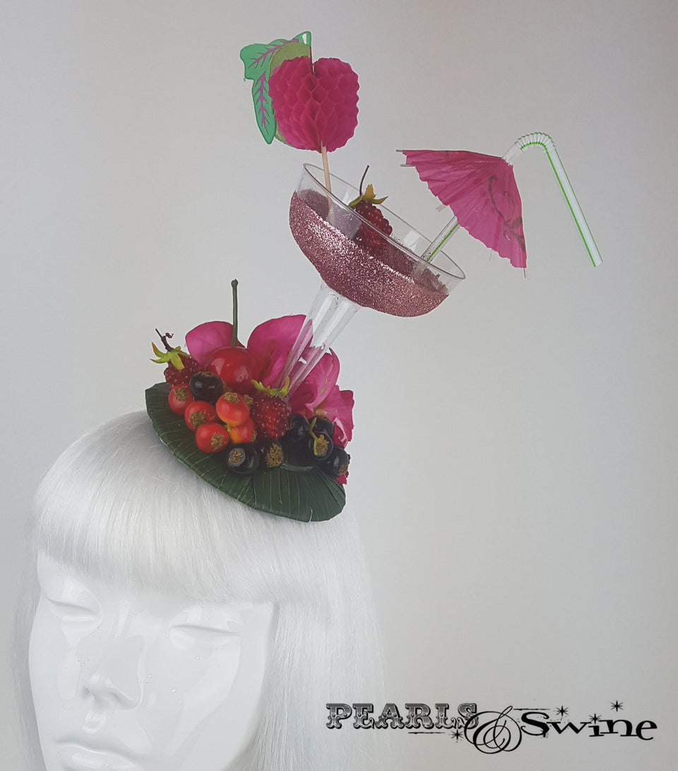 Pink glitter cocktail fascinator decorated with berries, cherries fruit, bougainvillea flowers and an umbrella