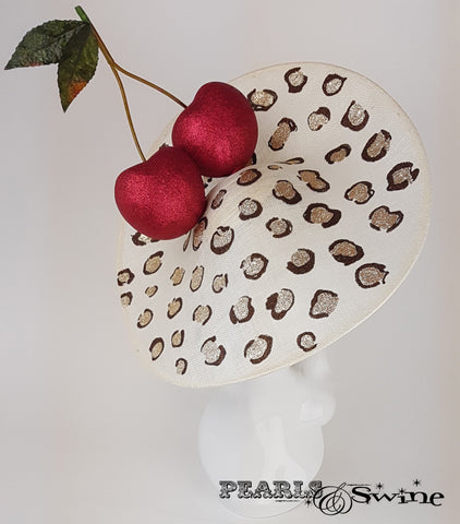 Giant red glittered cherries on a large ivory sinamay hat base, hand painted with glittered leopard print