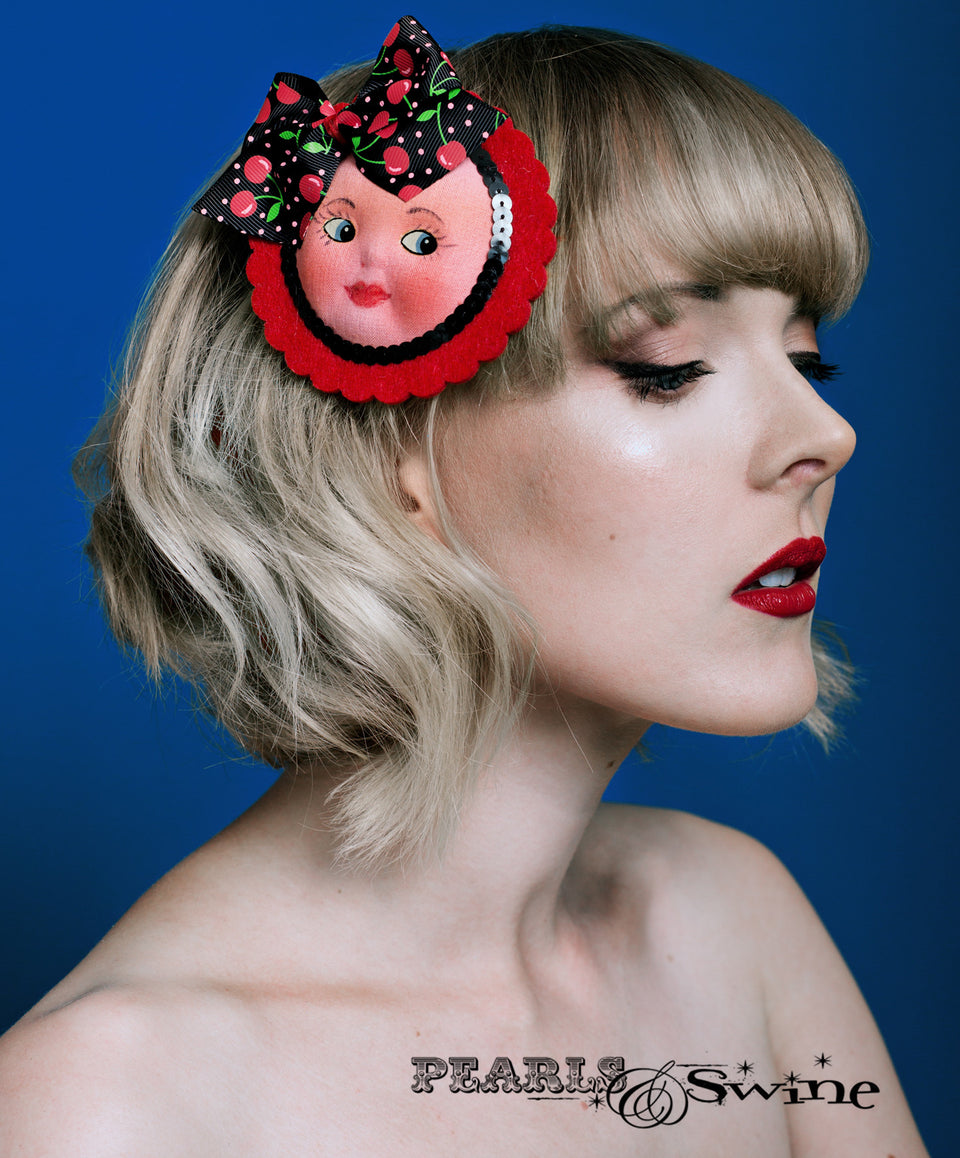 Cute vintage dollfaced hair clip, set on a red felt base and decorated with a black cherry covered bow and sequin