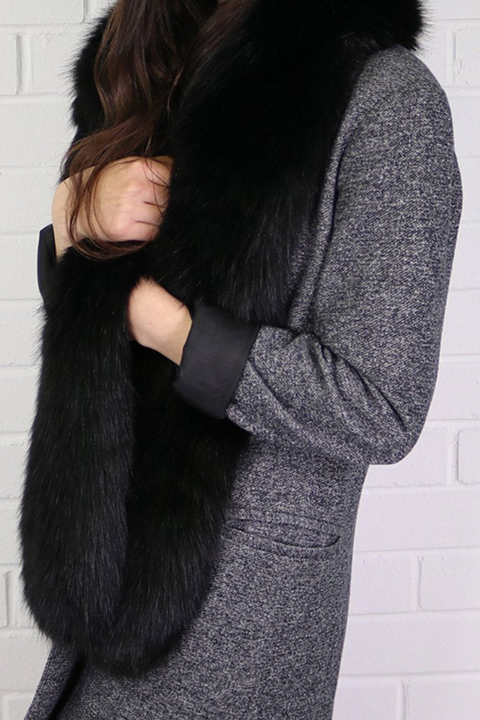 Model in grey coat wearing long black faux fur stole scarf