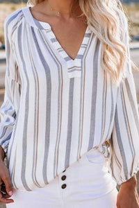 model wearing striped ecru grey and brown v neck shirt and white jeans