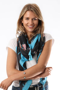 Model wearing a blue and grey scarf with flower print and tassels