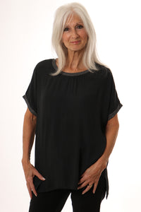 Model wearing dark grey short sleeve top with metallic trim on neck and sleeves