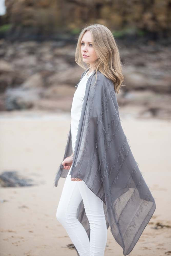 Model on beach wearing lightweight grey blanket scarf with tassel fringing all over