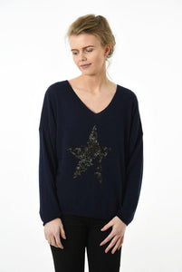 Model wearing navy long sleeve jumper with leopard print star on front
