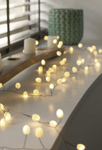 Opaque warm white teardrop fairy lights on shelf with candles and green vase