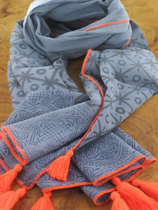 Dark grey cotton scarf with circle and star pattern and bright orange tassels and trim