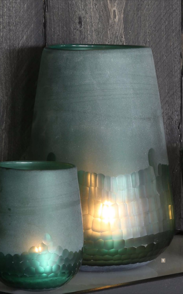 Green glass lanterns with lit candles on a shelf