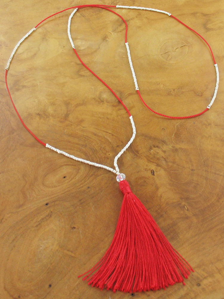 Thin long bead necklace with red tassel