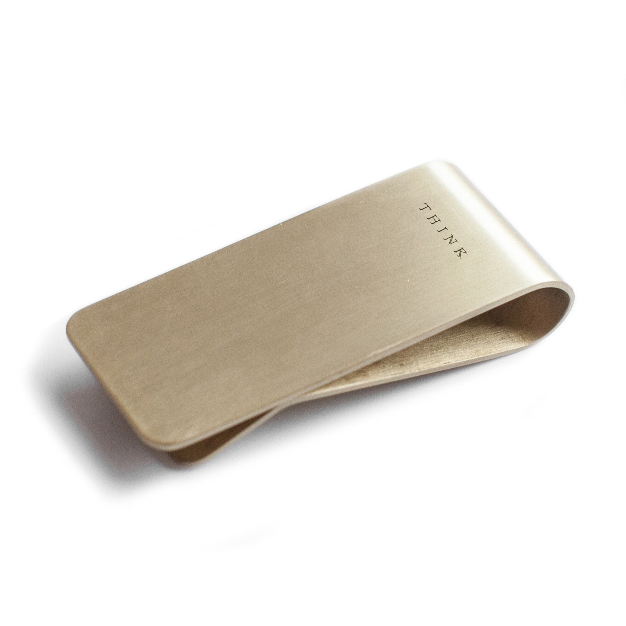 Brass money clip with think engraved on the front