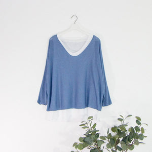 Blue lightweight jumper with white undershirt hanging on a hanger