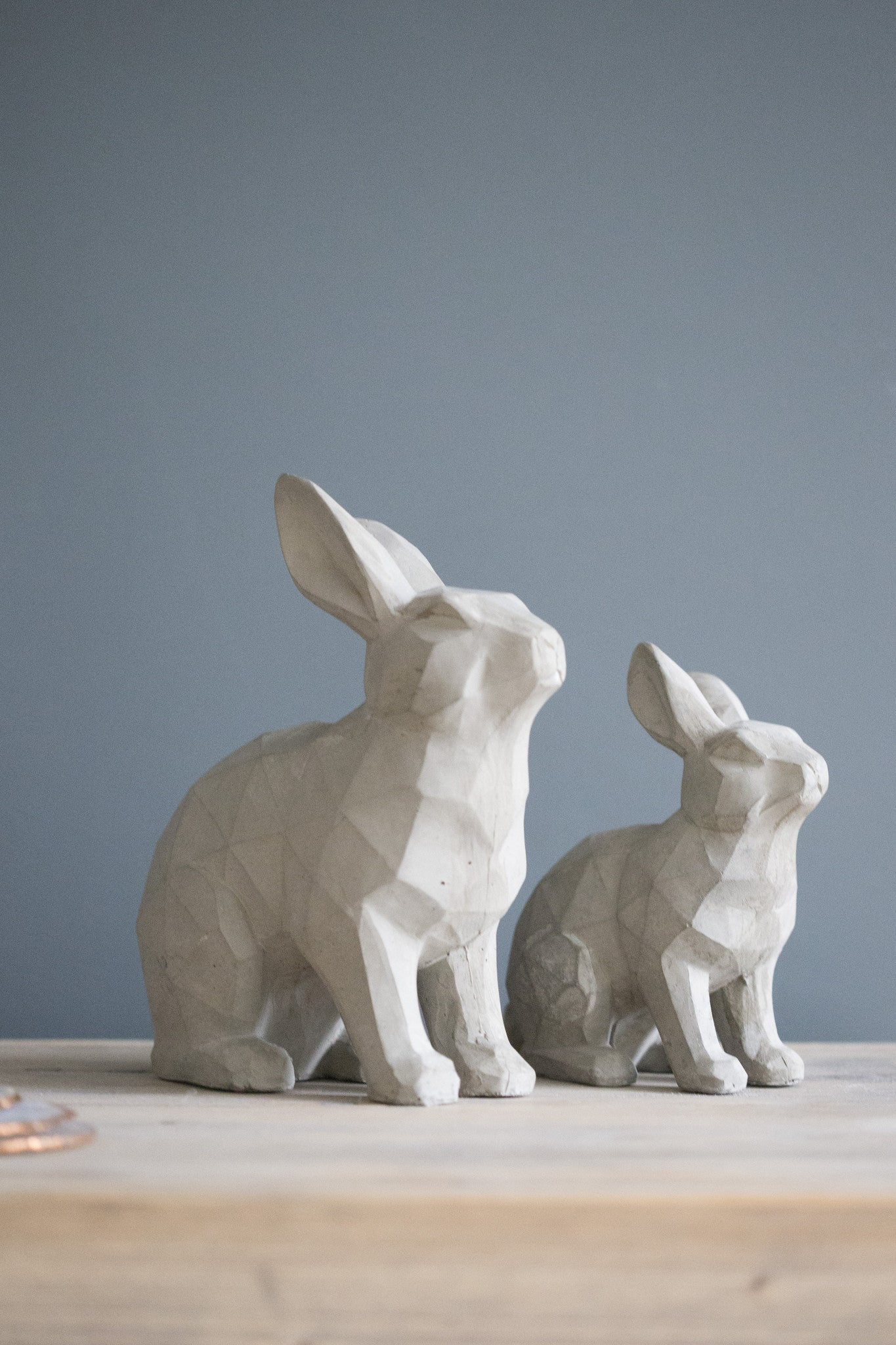 Large and small grey resin rabbits together on a shelf