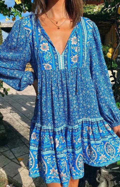 Model wearing a boho mini dress in blue floral print with v tie neck and long bell sleeves
