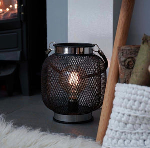 Black and chrome mesh lantern with battery operated LED bulb by fireplace