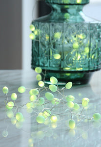Mint battery teardrop fairy lights draped out of green vase