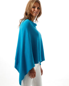 Model wearing white jeans and a lightweight cotton poncho in cyan blue