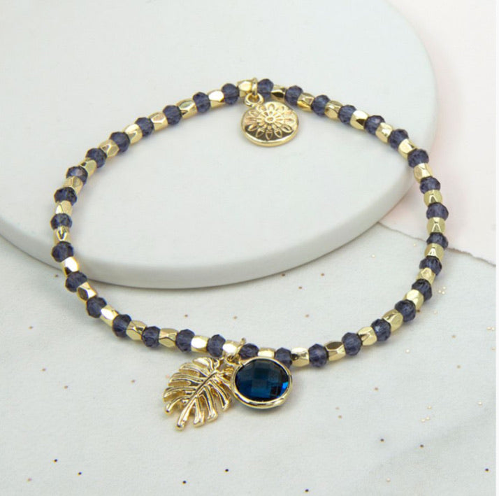Gold and navy blue stretch bead bracelet gold palm leaf and blue crystal charm