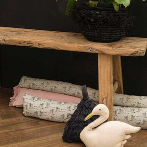 Grey draught excluder with flying geese design under wood bench