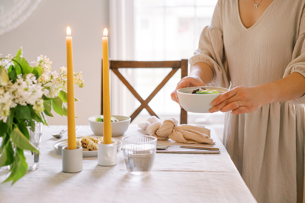 Woman setting down a bowl of soup on a table set with beeswax taper candles and a white floral arrangement.
