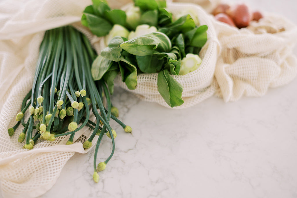 Chinese chives, bok choy, ginger and shallots in separate mesh grocery bags arranged on a quartz kitchen counter top.