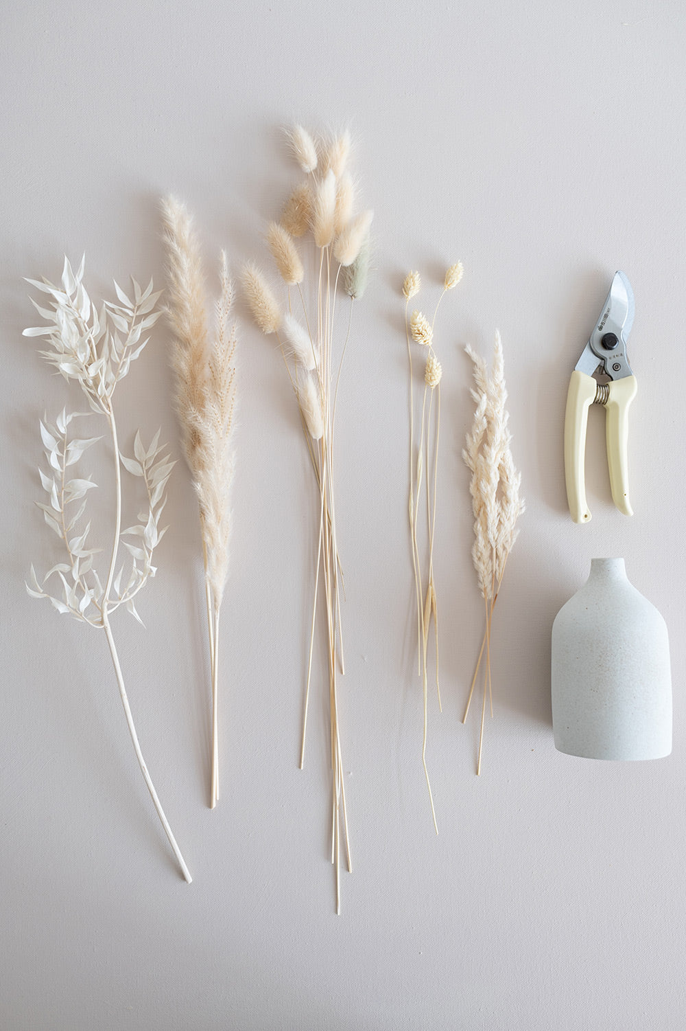 Assorted cream colour dried florals and grasses laid flat beside a pair of cream pruners and a white bud vase.