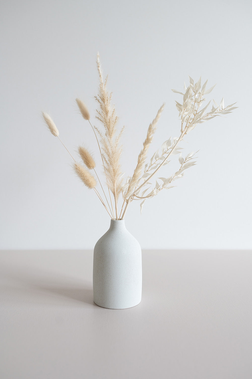 White bud vase with cream coloured bunny tails, pampas grass and white Italian ruscus.