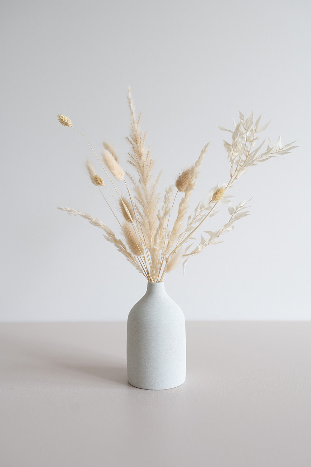 White bud vase arrangement of cream coloured dried florals and grasses.