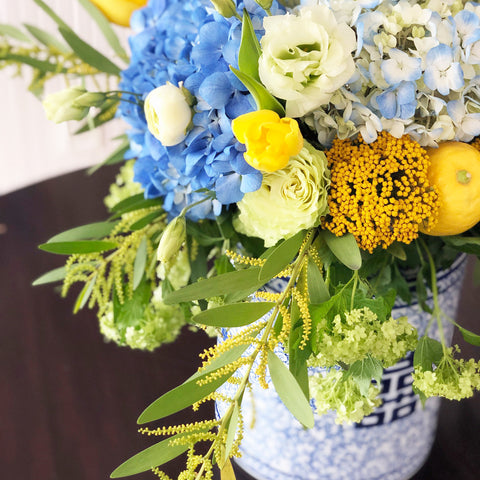blue and yellow centerpiece in ginger jar