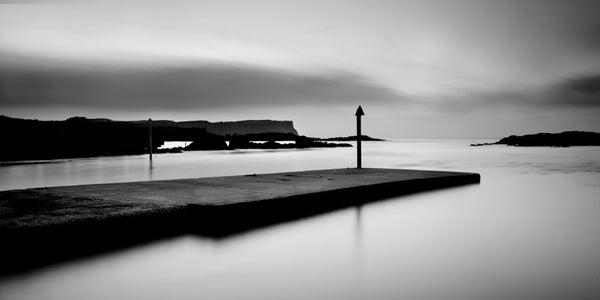 Monochrome image of Dunseverick Harbour at first light