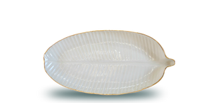 Handmade ceramic plate in the shape of a banana leaf, in a clear glaze, white colour, and an 18 karat gold rim around the edge. Great texture, feels good to the touch