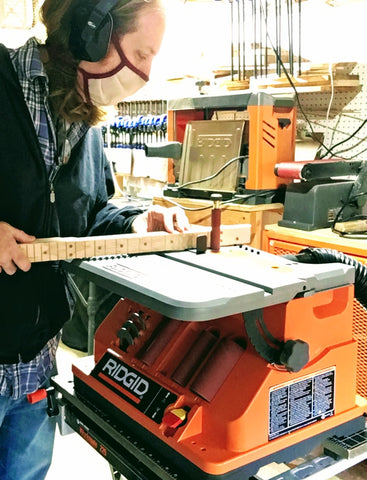 Mike Snowden working on a cigar box guitar neck at Snowden Guitars world headquarters.