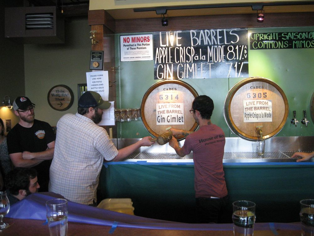 A customer takes a stab at tapping the keg at Cascade Barrel House weekly Tap it Tuesday event