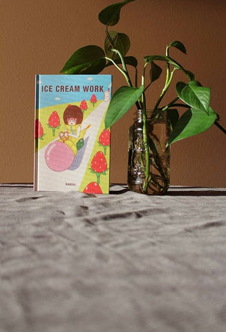 ice cream work sits back in the frame surrounded by green leaves