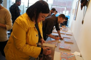 Beth Wagner, jewelry maker and featured Tall Trees of Portland artist, signing books at the artist book party