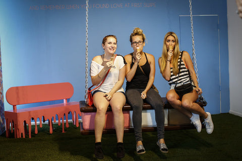 Visitors pose on an ice cream sandwich swing as they visit the Museum of Ice Cream across from the Whitney Museum on July 29, 2016 in New York City. The temporary museum dedicated to all things ice cream will be open for the month of August.