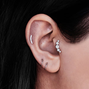 Ascension Tragus Helix & Conch Ear Piercing on model - titanium/crystal