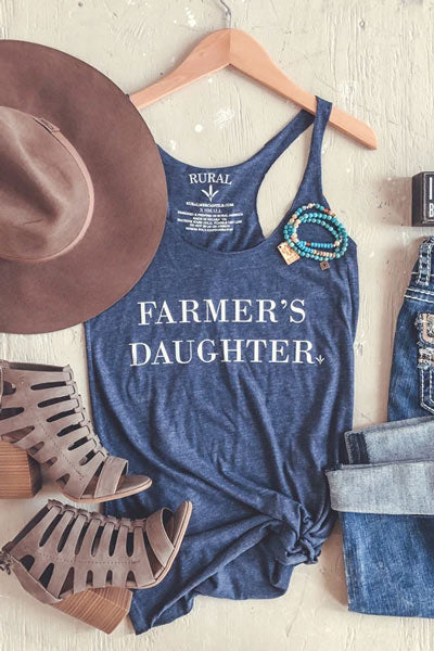 Blue graphic tank with heeled sandals and a brown hat.