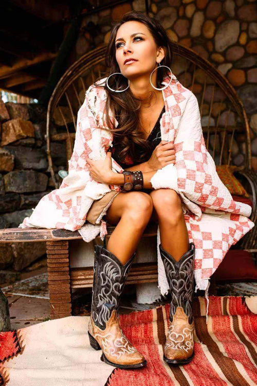 Woman wearing cowboy boots with a red & white blanket.