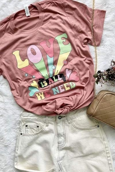 Pink graphic tee styled with white denim shorts