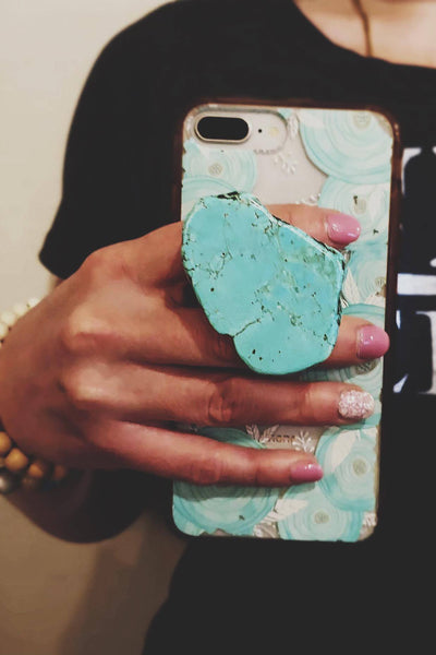 woman holding cell phone with natural turquoise phone grip