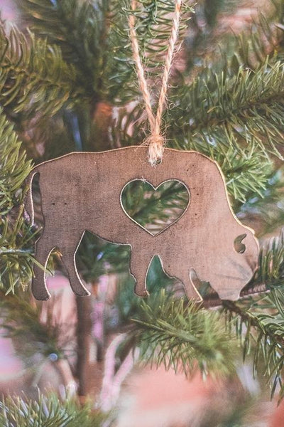 Rustic Buffalo Metal Christmas Ornament with heart cutout, hanging on Christmas tree