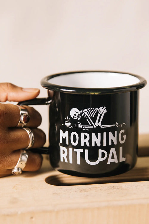 hand resting on table holding black enamel coffee mug with skeleton morning ritual printed design