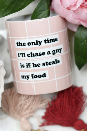 "Pink Coffee mug that says ""The Only Time I'll Chase a Guy is if he steals my food"" in front of Valentine's bouquet"