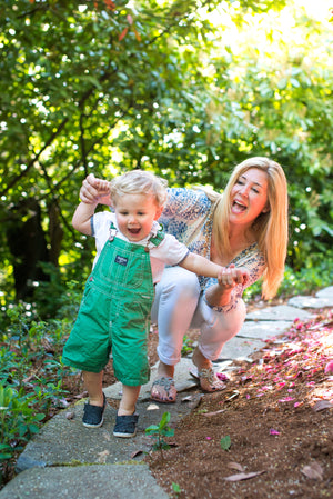 Joylux founder, Colette Courtion, with her son playing outside.